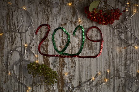 new year 2019 written with red and green sequins ribbons surrounded by lights and small red berries Stock Photo