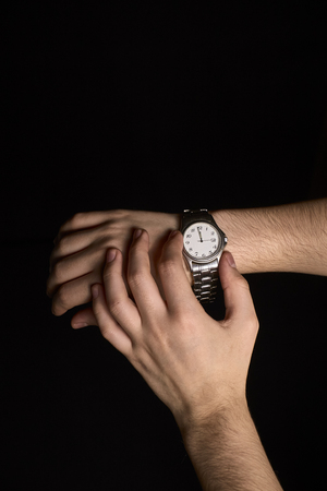 hands of a young person looking at a clock about to mark the first second of the new year 2019 with out of focus background lights Stock Photo