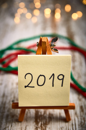 easel with yellow leaves written with the new year 2019 on a wooden table next to red and green ribbons and lights