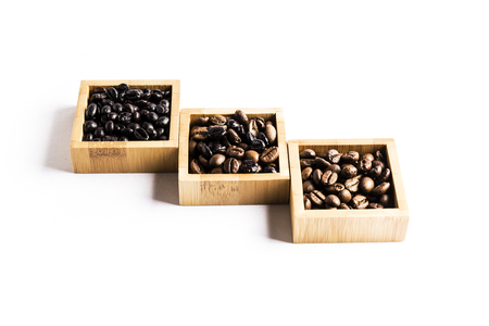 three groups of different coffee beans in wooden bowls on a white background