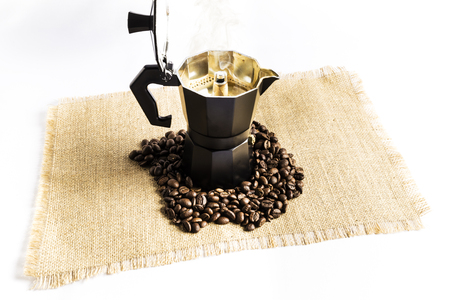 Italian coffee maker with hot coffee just made next to a pile of coffee beans on a cloth tablecloth