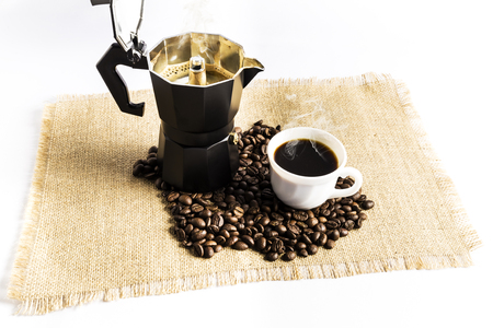 coffee beans next to an Italian coffee maker and a cup with coffee on a cloth tablecloth
