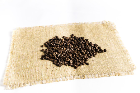 heap of coffee beans on a raffia cloth tablecloth on a white background
