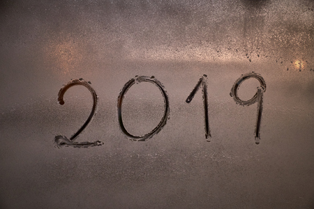 written the number of the new year 2019 on a window with a spray of foam at night in the light of the streetlights