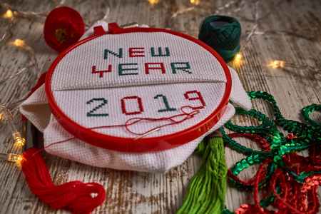 sewing by hand in white taper NEW NEW YEAR 2019 with red and green threads surrounded by party lights Stock Photo