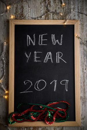 Black chalkboard with written words NEW YEAR 2019 surrounded by small lights and red and green quotes
