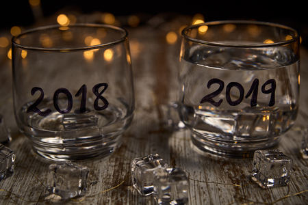 an almost empty glass of the year 2018 and another full of the new year 2019 surrounded by ice cubes and lights
