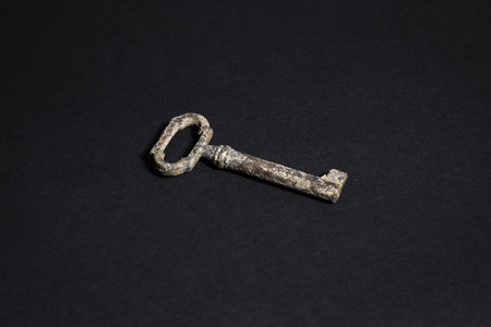 old rusty key of a door on a black background Stock Photo