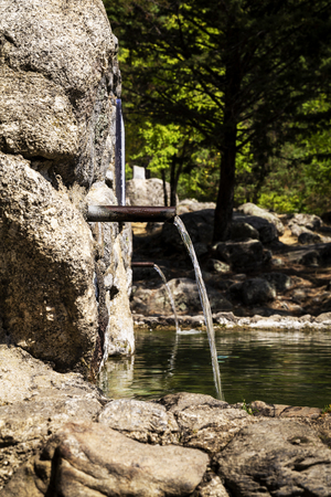 jet of fresh water coming out of a metal spout from a stone fountain in the mountain Stock Photo
