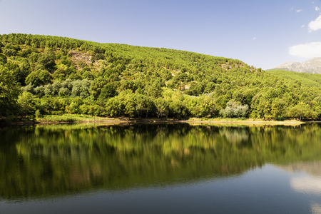 beautiful panoramic view of a lake surrounded by green mountains and a blue sky reflected in its waters Stock Photo