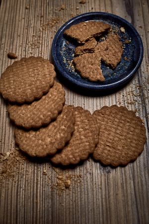 group of tasty cookies next to a bowl on an old wooden board