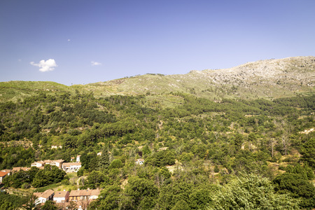 panoramic of a small town at the foot of a green mountain with a blue sky Stock Photo