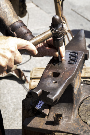 Blacksmith working on an old anvil next to his tools outside with daylight