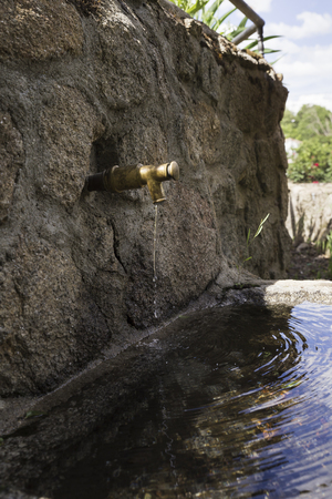 Stone fountain with an iron spout Imagens