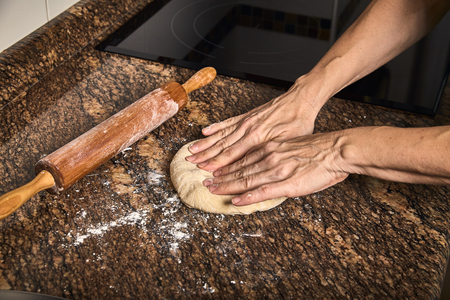 woman hands working on a dough to cook a tasty pizza Stock Photo