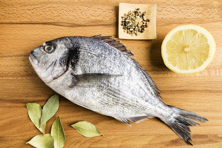 Dorada fresh fish next to some bay leaves, a piece of lemon and some spices on a wooden table