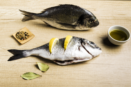 Two fresh fish Dorada with bay leaves, some pieces of lemon, a bowl of oil and some spices on a wooden table