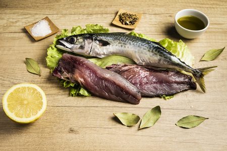Mackerel fresh fish on lettuce leaves next to bay leaves, a few pieces of lemon, a bowl of oil and some spices on a wooden table Reklamní fotografie