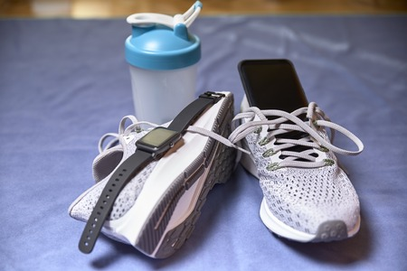 running shoes with technological accessories and next to a pot of water on a blue towel in a room