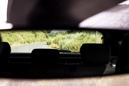 Rural road reflected in the mirror glass of a car parked on the shoulder