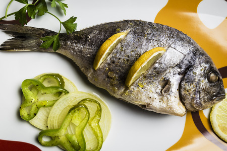 Dorada fish cooked in the oven with lemon, pimento and green onion served on a tray on a wooden table