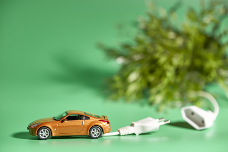 miniature of a vehicle with electric plug next to a plant on a green background 스톡 콘텐츠