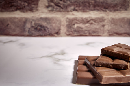 stack of tasty chocolate tablets on a white marble table