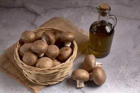 group of portobello mushrooms in a wicker basket next to an oil jar