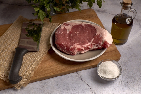 red veal chop on a plate on a wooden board