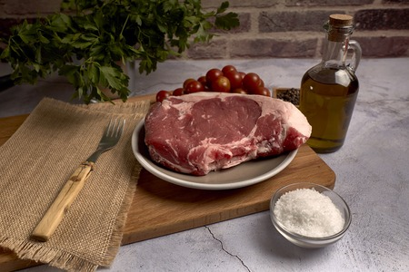 red veal chop on a plate on a wooden board Standard-Bild - 122574202