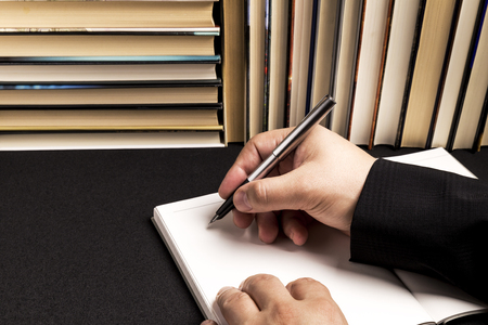 the hand of a man writing in a blank book beside a book background