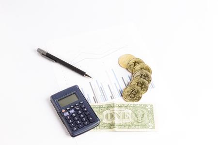 bitcoin gold coins on graph next to a calculator, a pen and a dollar bill Reklamní fotografie