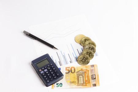 bitcoin gold coins on graph next to a calculator, a pen and a euro bill Reklamní fotografie