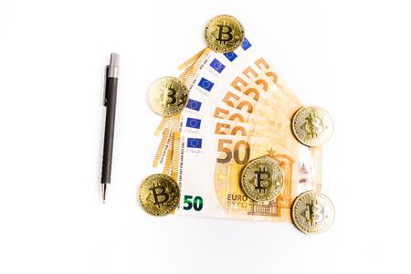 several bitcoin gold coins next to some euro bills and a pen