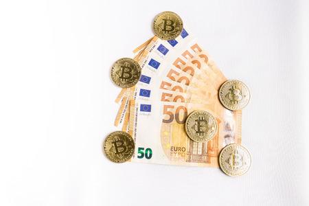 several bitcoin gold coins next to some euro bills Reklamní fotografie