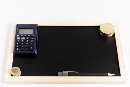 several bitcoin gold coins next to a calculator and a pen on a black chalkboard Reklamní fotografie