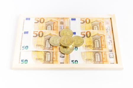 bitcoin gold coins on a box full of euro bills Reklamní fotografie