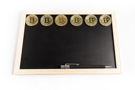 several bitcoin gold coins next to a pen on a black chalkboard Reklamní fotografie