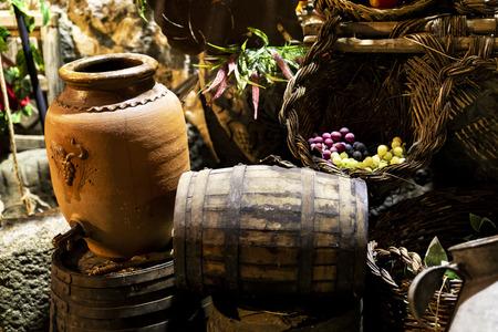 old clay pot next to wooden barrels to serve wine Reklamní fotografie
