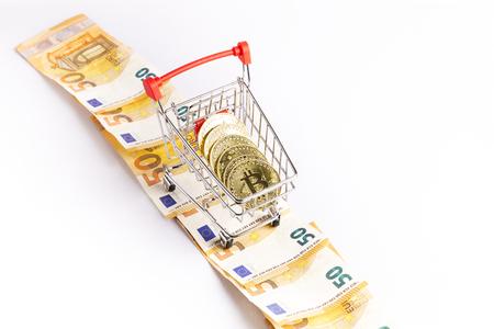 bitcoin gold coins in the shopping cart on a few euro bills Reklamní fotografie