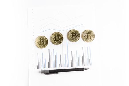 several bitcoin gold coins next to a pen on a graph Reklamní fotografie