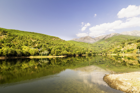 beautiful panoramic view of a lake surrounded by green mountains and a blue sky reflected in its waters Reklamní fotografie