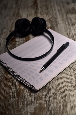 composition of black headphones next to an empty pentagram notebook on a wooden table