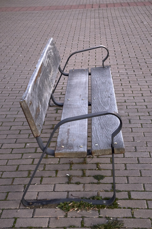 old empty wooden bench on the street of a city Stock Photo