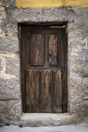 old brown wooden exterior door of a house with its rusty lock