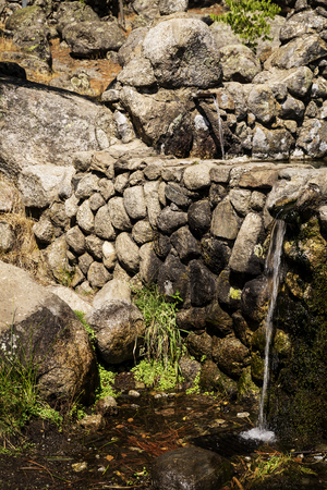 jet of fresh water coming out of a metal spout from a stone fountain in the mountain Imagens