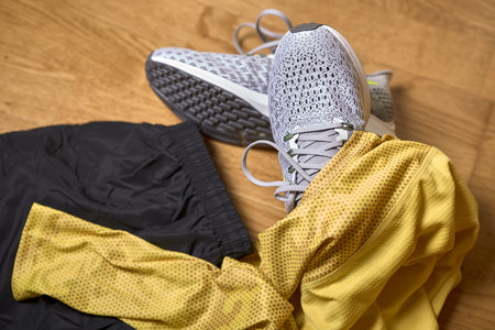 running shoes along with a shirt and shorts on a wooden gym floor
