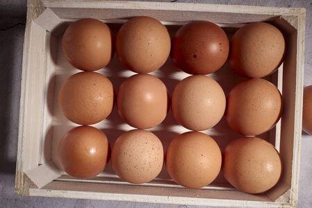 orange eggs of farm chicken inside a wooden box