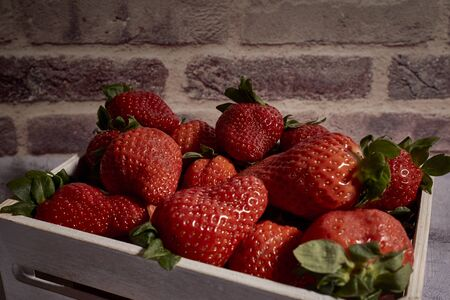 set of tasty red strawberries inside a wooden box
