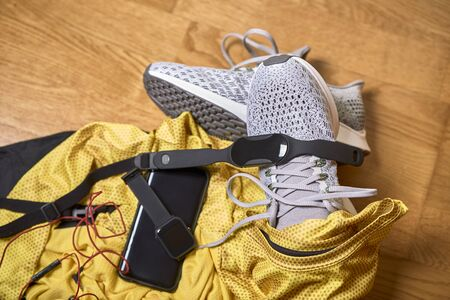 running shoes with a t-shirt, pants and technological accessories on a wooden gym floor